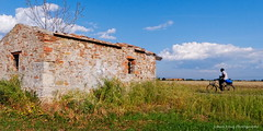 One Day in the Life of ... (Johan Konz) Tags: african refugee bike abandoned farmland shed building green grass blue sky white clouds vada tuscany italy outdoor landscape nikon d90 migration desolate displaced social perspective challenge