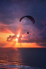 Crack the skye (Mimadeo) Tags: paraglider paragliding parachute gliding yellow blue sunrise silhouette wind sport flight freedom cloud air dusk free sunlight glide adventure action risk ray colourful sea beam vivid vibrant sunset sky fly orange extreme sun glider wing