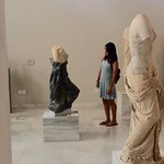 An Honors student gazes at a sculpture in a museum in Athens.