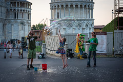 Popping Bubbles (Zano91) Tags: center centre history sun ray rays reflecting reflections nikon d7100 sigma 1835 f18 italy italia buildings architecture grey cloud clouds streets alleys lamp blue red bricks windows tower estense road outdoor building miracoli piazza pisa dome leaning famous girl street bubble bubbles soap play playing jump
