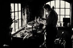 The Leather Belt Maker (Jonsel) Tags: bw leatherwork industry old crafts skills workshop workman craftsman moody noir blackandwhite windows windowlight candle candlelight