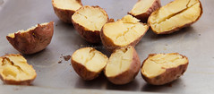 Baked potatoes. (annick vanderschelden) Tags: potato unwashed dirty starchy tuberous crop perennial nightshade solanumtuberosum edible tuber andes species indigenous food foodsupply foodcrop soil whitebackground structure starch vitamins minerals phytochemicals carotenoids naturalphenols vitaminc potassium carbohydrate resistantstarch fiber glycemicindex culinary skinon cooking whole red ovenplate hot baking baked cut halves