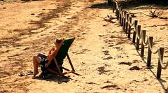 Life's A Beach (acwills2014) Tags: beach sunshine legs lady relax fence lifesabeach fencefriday deckchair sand driftwood sunbathing solitude shadows seaweed attractive beachscene