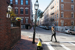 Uphill Battles (ahh.photo) Tags: yellow flowers city people street travel house tourist urban architecture lights road plants building woman brick pavement town hill outdoors horizontal crossing perspective slope fujifilm boston beacon xf 14mm f28 r xt1