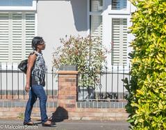 The Girl & Her Shadow (M C Smith) Tags: k3ii road house shadow wall pavement woman pentax bushes windows railings shutters yellow green