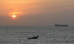 MARINE CLOUD COMING IN.    SUNSET IN PORT OF  DAKAR,  SENAGAL.  (FISHERMEN IN THEIR WOODEN BOAT, AND A CONTAINER SHIP. ) (vermillion$baby) Tags: nativeboat atlantic boat color dakar dugout harbour ocean port sea senagal ship silhouette son sunset vessel coasr sunrise senegal orange coast cloud