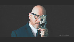 """A camera teaches you to see without a camera."" (MrPessimist) Tags: nikon d7100 nikond7100 nikonuser nikonphotography portrait portraitphotography strobe strobist strobes alienbees paulcbuff camera male man glasses selfportrait suit suittie tie bald beard letterbox 169"