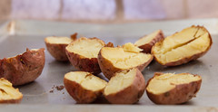 Baked potatoes cut into halves. (annick vanderschelden) Tags: potato unwashed dirty starchy tuberous crop perennial nightshade solanumtuberosum edible tuber andes species indigenous food foodsupply foodcrop soil whitebackground structure starch vitamins minerals phytochemicals carotenoids naturalphenols vitaminc potassium carbohydrate resistantstarch fiber glycemicindex culinary skinon cooking whole red ovenplate hot baking baked cut halves