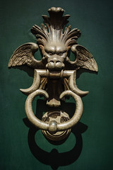 Serious (Мaistora) Tags: door knocker bronze detail fragment cast casting brass alloy gold mythical creature green metal relief structure texture shape art sculpture design classic medieval historic antique old typical light shadow angle eyes angry serious menacing wings winged head walkby passingby street city urban centre milan milano lombardia lombardy italy italia sony ilce alpha a6000 sel1650pz lightroom