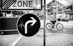 Zone focusing (Mister G.C.) Tags: street urban photography blackandwhite bw germany ricoh ricohgr streetphotography urbanphotography candid shot image photograph people bike pushbike bicycle arrow roadsign juxtaposition monochrome town city zonefocus zonefocusing snapfocus pointshoot mistergc schwarzweiss strassenfotografie niedersachsen lowersaxony deutschland europe
