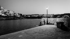 Naousa port fisher (F719D) Tags: street streetphotography bw blackandwhite blancoynegro black white old port sea rocks fish fishing fishingman fisherman night sunset greece paros island streetlight