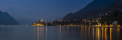 Malcesine in Blue II (Explore 21/07/17 #18) (andyrousephotography) Tags: italy lakegarda lake malcesine town harbour lamps promenade vialungolago evening dusk bluehour castle illumination mountains montebaldo paddleboarders blurred panorama stitched andyrouse canon eos 5d mkiii ef70300mmf456l