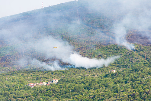 Fire-fighting plane dumping water on forest fires on hills around Bay of Kotor, Montenegro, July 2017