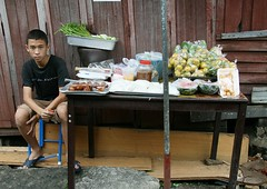 boy selling food and not looking very happy about it (the foreign photographer - ฝรั่งถ่) Tags: boy seated selling fod khlong thanon portraits bangkhen bangkok thailand canon kiss