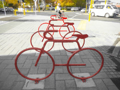 Bike Riding (Steve Taylor (Photography)) Tags: helmet van trafficlights art sculpture road path street grey yellow white red block woman lady newzealand nz southisland canterbury christchurch cbd city texture bike bicycle cycle rider sunny sunshine rack