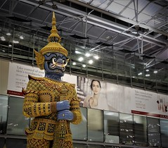 beauty and the beast (SM Tham) Tags: asia southeastasia thailand bangkok suvarnabhumi airport terminal building interior statue thai mythology god dewa advertisements billboards lady
