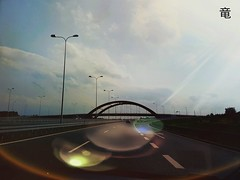 road towards sunshine (Ola 竜) Tags: road highway sunlightflare sunshine flare landscape sky clouds way horizon skyscape sunset afternoon sunny dusk evening bridge cars ride ontheroad car architecture urban view perspective driverspov lampposts citylimits bokeh lines signs sunrays beams eye