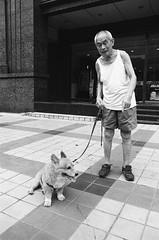 "Elderly man with his dog on Wangfujing, Beijing (Xsbmrnr (Please read profile before ""following"") Tags: film 35mmfilm ishootfilm china chinaimages chinesestreetshots blackandwhite bandw blazinal jch400streetpan olympusom1 olympus om1 people dog dogs wangfujing"