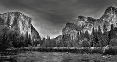 Standing on the Banks of the Merced River and Taking in an Amazing View of Mountain Peaks (Black & White, Yosemite National Park) (thor_mark ) Tags: nikond800e day5 triptopasoroblesandyosemite yosemitenationalpark lookingeast capturenx2edited colorefexpro silverefexpro2 blackwhite outside trees hillsideoftrees blueskieswithclouds grassymeadow nature landscape mercedriver river bridalveilfall waterfall 617ft188metres ahwahneecheenamepohono spiritofthepuffingwind 3000feethighgranitemonolith 900meterhighgranitemonolith elcapitan salathžwall totokonoolah mountains mountainsindistance mountainsoffindistance lowercathedralrock middlecathedralrock uppercathedralrock cathedralrocks riverbank pacificranges sierranevada yosemiterittersierranevada centralyosemitesierra yosemitevalley project365 portfolio canvas california unitedstates salathéwall