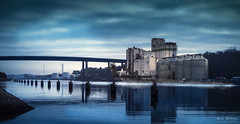 Grain Elevator [Kiel Canal] (Nils Hempel | Photography) Tags: deutschland kiel water germany blue colorful building architecture industry reflections sky clouds landscape panorama panoramic bridge europe travel outdoor light
