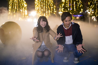 High school couple playing in fog under Christmas lights