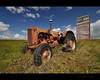 this temporary life (Gordon Hunter) Tags: orange red tractor farm prairies grain elevator old abandoned temporary summer sun midday sky grass wide angle wooden dankin saskatchewan sk canada gordon hunter nikon d5000