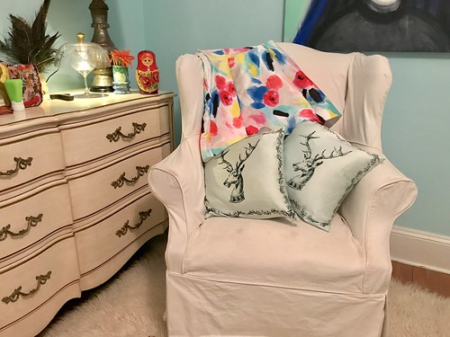 kate spade party dress on slipcovered chair with two decorative elk pillows