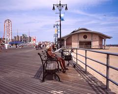 Guy in the sun (Brad Chaffin) Tags: coney island coneyisland 120film mediumformat mamiya7 slidefilm beach boardwalk tan sand ocean film newyork fujivelvia100