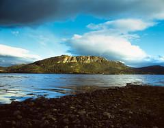 The Shoreline of Loch Carron (Benjamin Driver) Tags: velvia film slide slidefilm analogue expired 120 medium format mediumformat 6x7 67 6 7 pentax pentax6x7 pentax67 45mm wide scan colour complementary colours blue dark cloud clouds loch carron lochcarron contrast scotland highlands naturallight