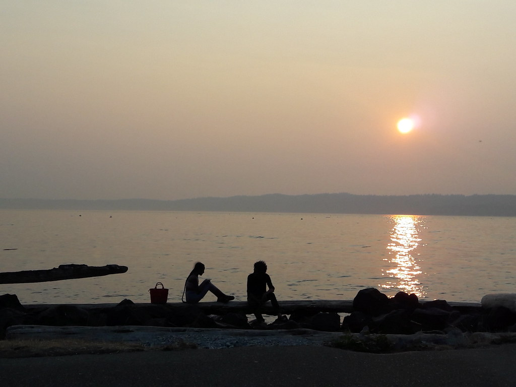 Silhouettes of a woman and man, smokey sunset on the beach, Saltwater State Park, South Des Moines, Washington, USA