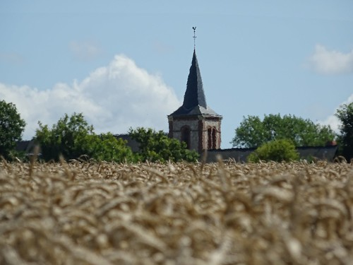 The heat above a field blurs a church behind