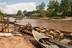 Thailand sacks of grain are slid down a chute to be loaded onto a longtail boat to cross the Moie River for export to Myanmar. (JJ Doro - Bangkok) Tags: burma burmese maesot moieriver myanmar seasia thailand asia asian asianmarket export import trade tambonthasailuat tak th