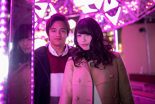 High school couple standing under pink Christmas lights