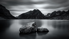 Tranquility (One_Penny) Tags: adventure arctic canon6d greenland hiking landscape mountains nature northpole outdoor photography phototour travel black white monochrome water fjord surface rocks stones sky clouds dark longexposure photoworkshop calm peace tranquility blackandwhite bw minimal mountainscape