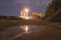 Secret life of a puddle (Markus Lehr) Tags: puddle gravelprocessingplant silos trees notsoemptyforeground light mounds nopeople peoplelessness humanartifacts manmadelandscape night nightphotography nightshot longexposure ostrava czechrepublic markuslehr