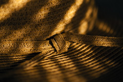 Sun hat in sunrise light on table with light streaks and close u (Jim Corwin's PhotoStream) Tags: artsandcrafts beige bow brown closeup contrast highlightsandshadows knot lightpatterns morninglight selectivefocus simplicity sunprotection sunlight texture textured tied warmlight wearforprotedtion woven wovenpatterns