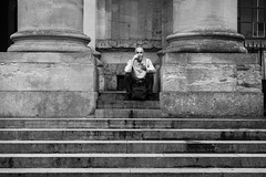 Between Pillars (Cliff.j) Tags: man smoking pillars concrete oxford city street sitting clarendon building candid architecture steps bald sony a7 mirrorless carl zeiss sonnar 55mm
