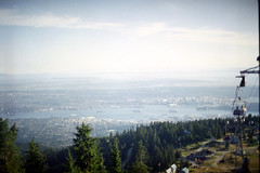 Grouse Mountain 5: Vancouver and Burrard Inlet (pmvarsa) Tags: vancouver bc britishcolumbia burrardinlet burrard inlet 1998 summer pacific ocean city downtown stanley park stanleypark northvancouver north film kodak gold kodakgold200 135 35mm analog water gondola lift sky blue trees green outside canon ftb fd cans2s classic camera tourism nikonsupercoolscan9000ed nikon coolscan west coast shipping ships boats grouse mountain