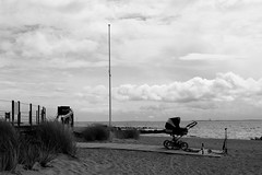 Buggy at the Beach (Von Noorden) Tags: noiretblanc einfarbig wand black white blackandwhite bw sw schwarzweiss topv germany schwarz weiss weis schwarzweis shade monochrome plain beach neustadt holstein lübeck strand promenade promenaden scooter stroller pram baby carriage pushchair buggy clouds dune dünen nobody summer coast fence scene perambulator child children playground toy toys water ostsee baltic sea