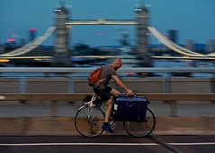 Man on bike at night with suitcase (jeremyhughes) Tags: london londonbridge night nighttime evening dark bicycle bike cyclist cycling towerbridge suitcase movement motion panning speed street bridge lights gloaming portage carrying luggage loaded transport laden nikon d750 nikkor afzoomnikkor80200mmf28ded people city cityscape