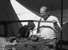 BLACKSMITH, MEDIEVAL FAIR, BOLSOVER CASTLE_DSC_6135_LR_2.0 (Roger Perriss) Tags: bolsovercastle joust medieval people d750 blackandwhite fair fire furnace coals charcoal bellows workman craftman