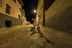 Noches de verano..... (Martika64) Tags: noche fotografíanocturna verano luces farolas calle triciclo infancia pueblo edificios largaexposición night nightphotography summer lights lampposts street tricycle childhood town village buildings longexposure outdoor noperson