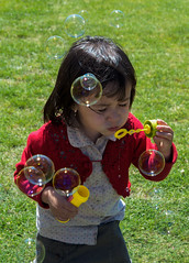 Childish Games (Girl) (Ganymede Photography) Tags: kid kids portrait portraits child children childhood nikon d60 green grass blowing blow bubble bubbles nature joy enjoy enjoying enjoyment play playing outdoors day daytime parla madrid spain innocence innocent playful red yellow color colors colorful happy happiness park cute girl pretty game two three years old toy family familiar childish blower