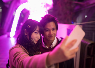 High school couple taking selfie picture under Christmas lights