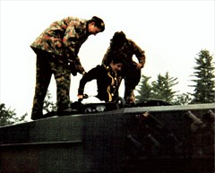 Deborah Eadie is helped into the turret of a tank (photo by Roger Johnson)