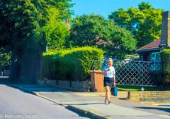 Modern Communication 2 (M C Smith) Tags: woman pavement trees green sky blue pentax k3ii road kerb garden weeds fence wall bin brown shadows walking phone bag houses