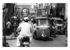into hyderabad (handheld-films) Tags: india old hyderabad city cities streets indian blackandwhite monochrome arch bikes subcontinent travel transport tuktuks people traffic