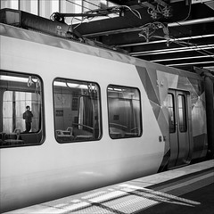 ringwood-8501-bw-ps-w (pw-pix) Tags: person man boy passenger waiting station trainstation railwaystation train carriage carriages pantograph insulators wires doors seats interior exterior windows reflections platform overhead wiring lights signs map networkmap tactiles building wall new winter ringwoodstation ringwood easternsuburbs melbourne victoria australia