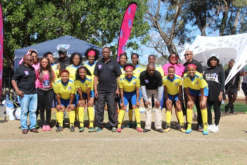 The Honourable Minister of Sports (centre) posing with one of the participating teams
