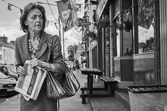 Irland Street Ennis Frau 249 b&w (rainerneumann831) Tags: irland bw blackwhite ©rainerneumann street streetscene urban monochrome candid city streetphotography blackandwhite ennis frau zeitung portrait